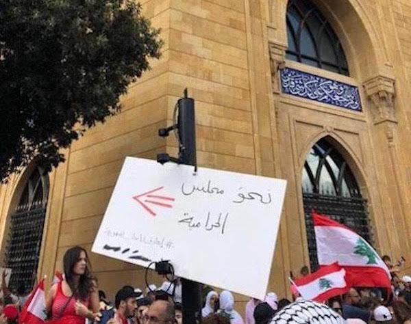 Crowd with sign in protest against Lebanon's government
