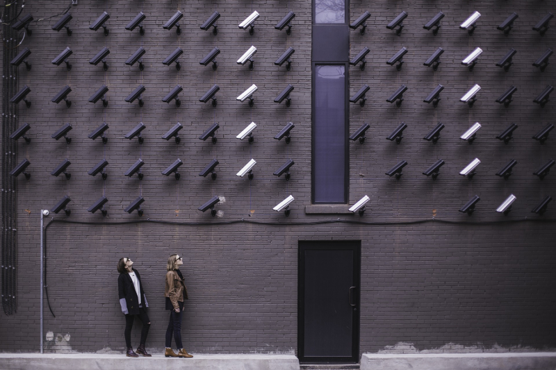 Two people looking up at a wall filled with security cameras