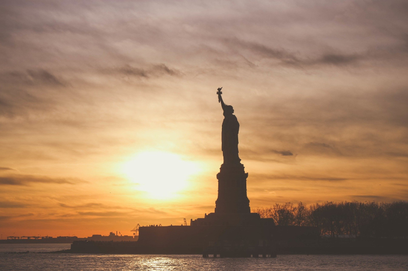 The Statue of Liberty in silhouette at sunset