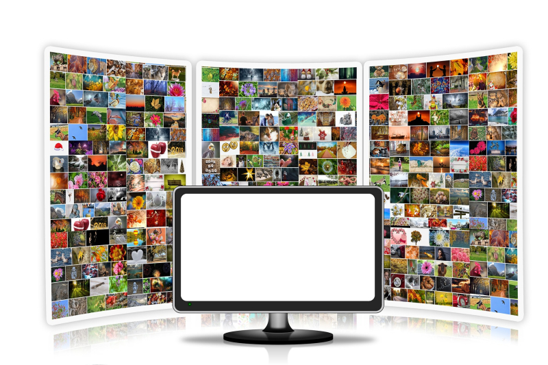 A large blank computer monitor sits in front of a background filled with many small, colorful pictures